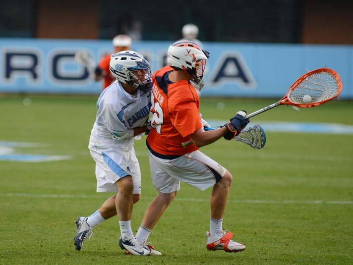 UNC attacker Jimmy Bitter (4) forces a turnover from Virginia goalkeeper Rhody Heller (42).