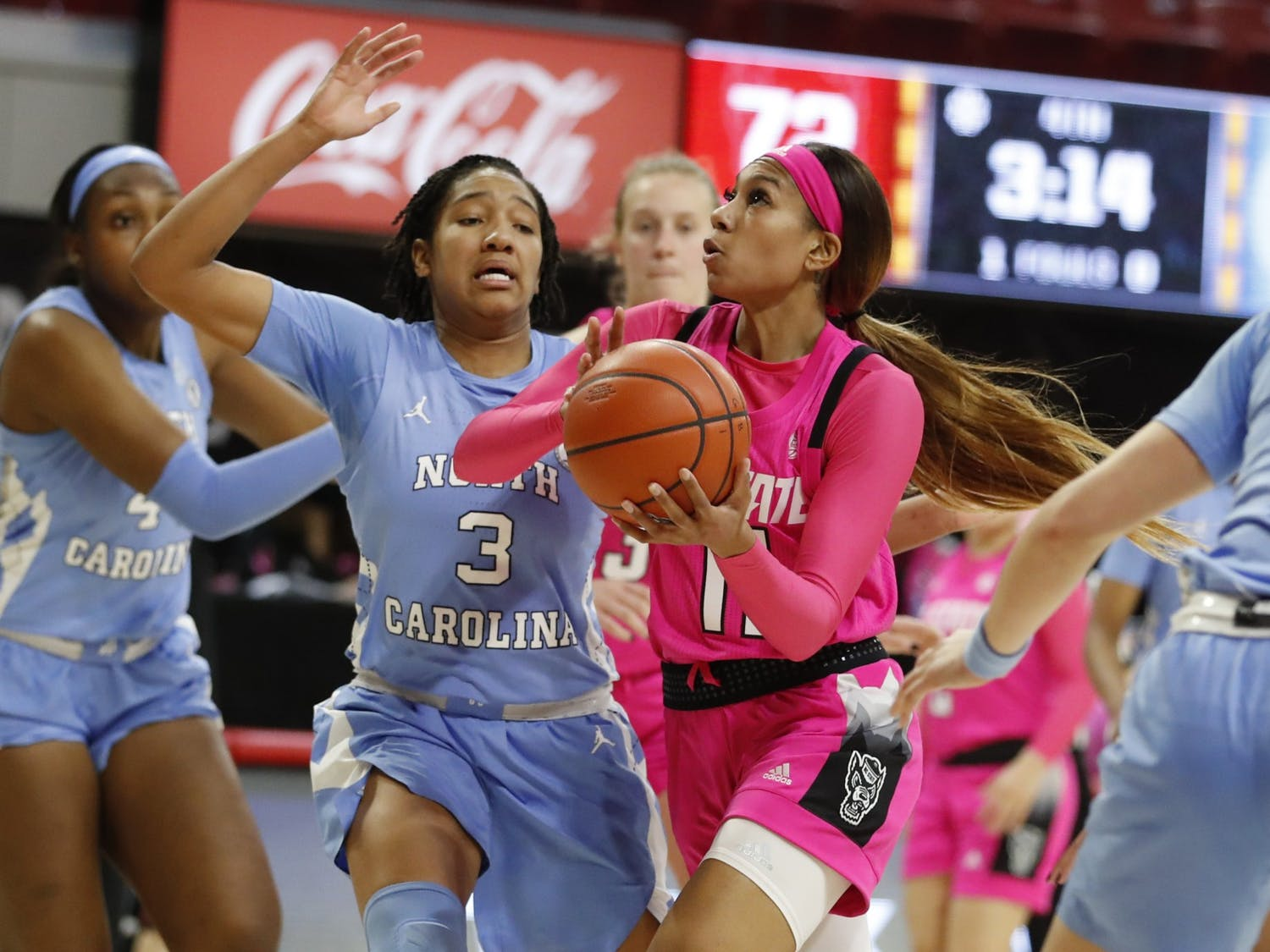 N.C. State's Jakia Brown-Turner (11) drives to the basket past North Carolina's Kennedy Todd-Williams (3) during the second half of N.C. State's 82-63 victory over UNC in the annual Play4Kay game at Reynolds Coliseum in Raleigh, N.C., Sunday, February 21, 2021. Photo courtesy of Ethan Hyman.
