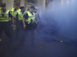 A smoke grenade deployed by the police to disperse the angry crowd of counter demonstrators fills the air with blue smoke on Saturday, September 8th.