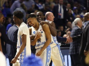 North Carolina wing Theo Pinson (1) and guard Nate Britt (0) celebrate after defeating Arkansas in the second round of the NCAA Tournament in Greenville on Sunday.Trailing 65-60 with 3:28 left, UNC closed the game on a 12-0 run to beat Arkansas.