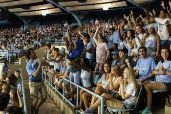 Sophomore Gray Forrester (left) prepares to throw a towel into the crowd of first-year students at New Student Convocation on Sunday, Aug. 21, 2016.