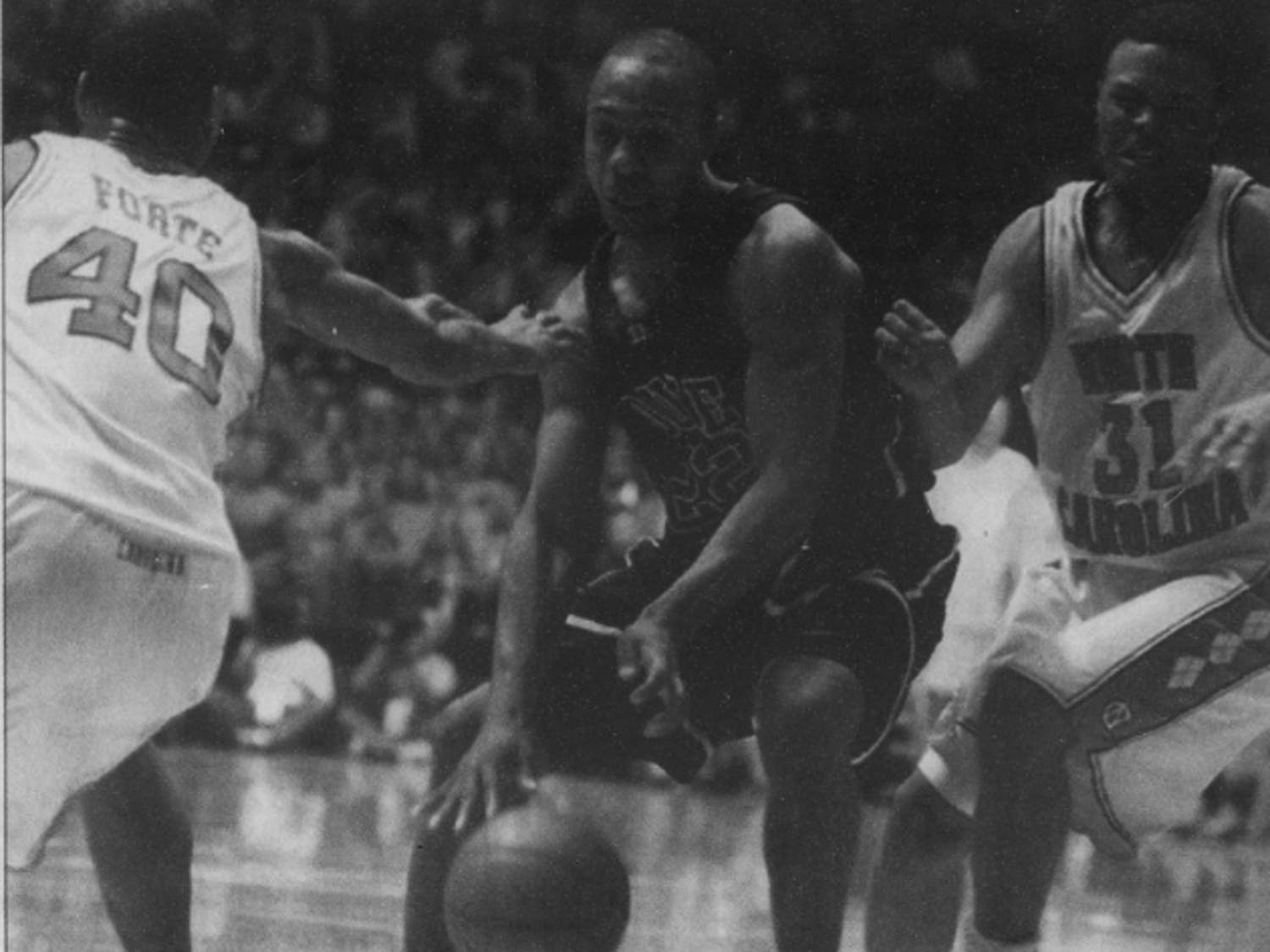 DTH Archive. North Carolina sophomore Joseph Forte (40) tries to help Adam Boone guard Duke point guard Jason Williams (22). Photo by Emily Schnure.