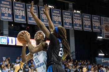 UNC first-year forward Malu Tshitenge (21) eyes the net with Duke University sophomore forward/center Onome Akinbode-James (24) on defense in Carmichael Arena on Sunday, March 1, 2020. The Blue Devils beat the Tar Heels 73-54.