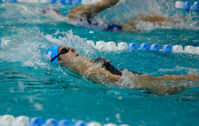 Sophie Lindner competes in the 100 yard backstroke event during the home swim and dive meet vs. Duke in Koury Natatorium on Saturday, Feb. 2, 2019.