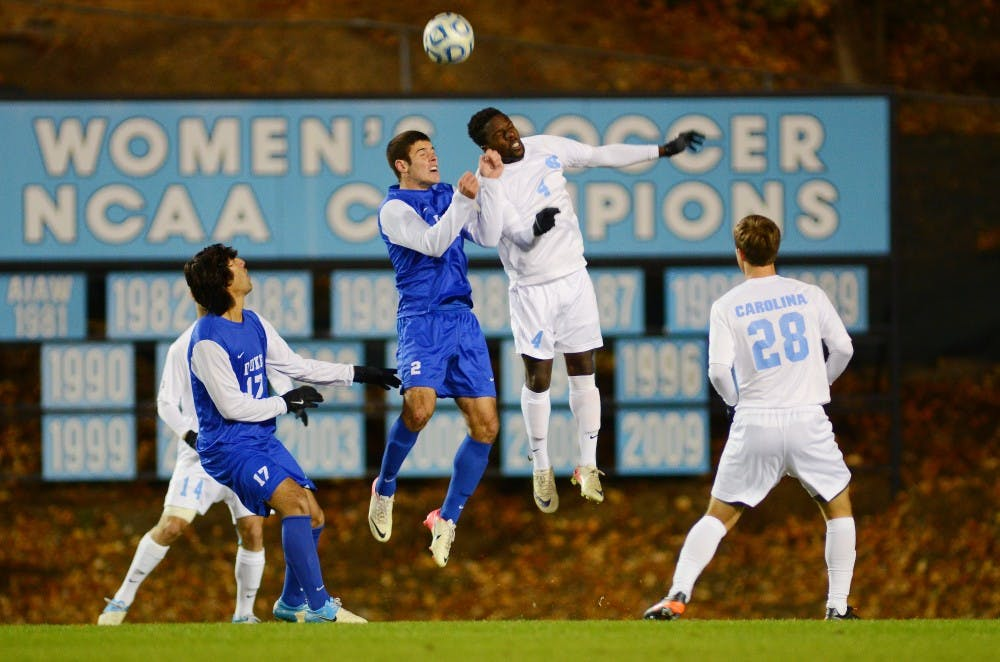 <p>North Carolina defender Boyd Okwuonu leaps to fend off Duke's Will Donovan as UNC's Alex Olofson waits to recieve the ball in the Tar Heels' 1-0 victory.</p>