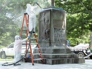 Workers remove graffiti from the Silent Sam monument on Tuesday.