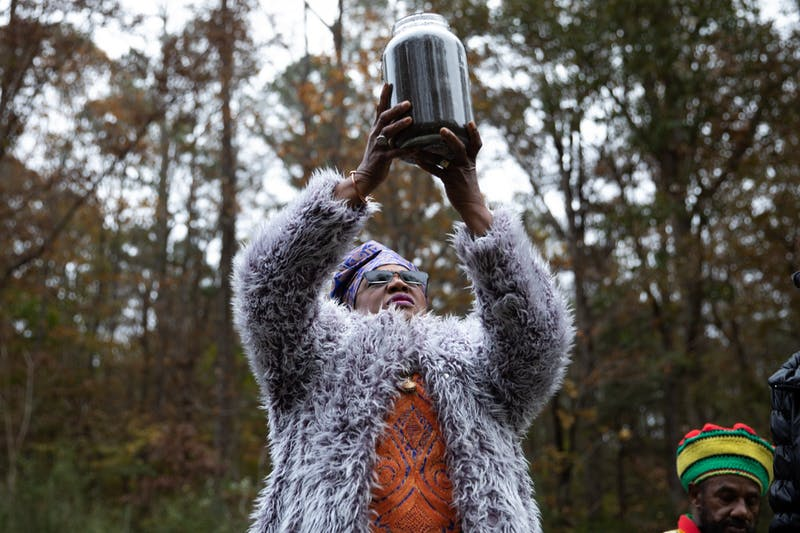 """For out of the soil comes life,"" Elder Malika Mills says as she holds a jar of soil above her head during a soil collection ceremony at Carl Drive in Chapel Hill on Saturday, Nov. 16, 2019. Descendants of Manly McCauley and members of the community gathered during the private ceremony to gather soil from the site where they believed McCauley was lynched by a white posse in the late 19th century."