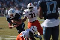 Carolina quarterback Nathan elliott (11) pulls away from Miami defense