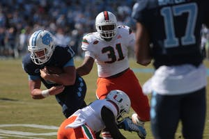 Carolina quarterback Nathan elliott (11) pulls away from Miami defense