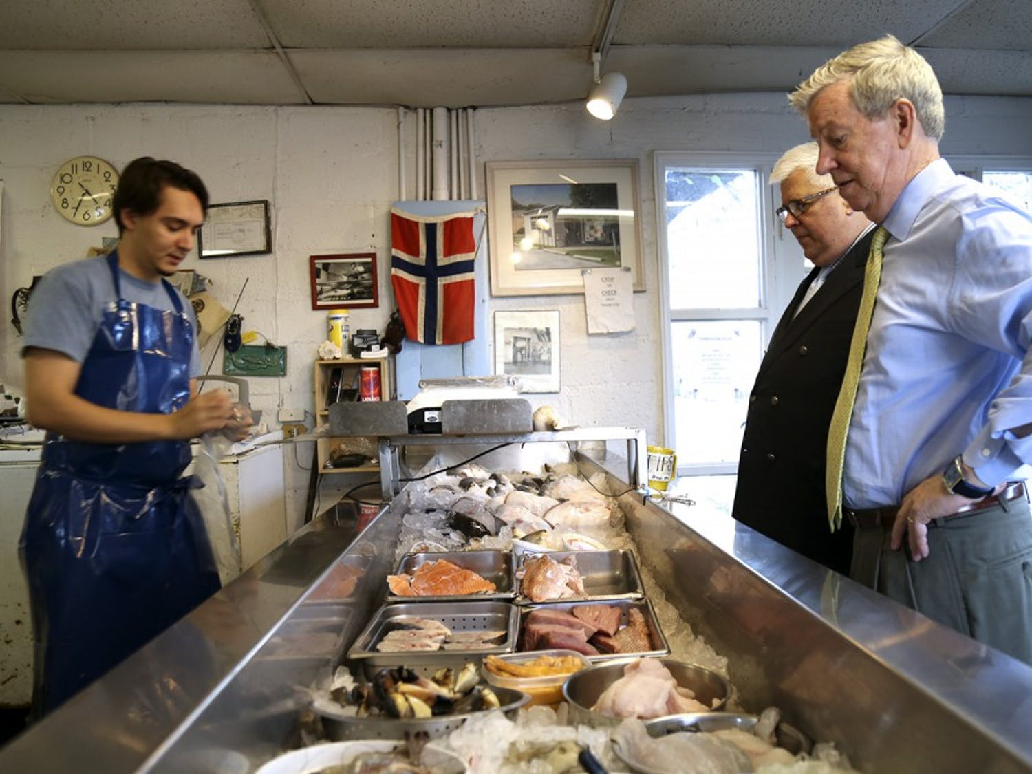 (From left) Sam Sockwell, a worker for Tom Robinson's Sea Food, works behind the counter for Mark Pandick and Larry Logan.