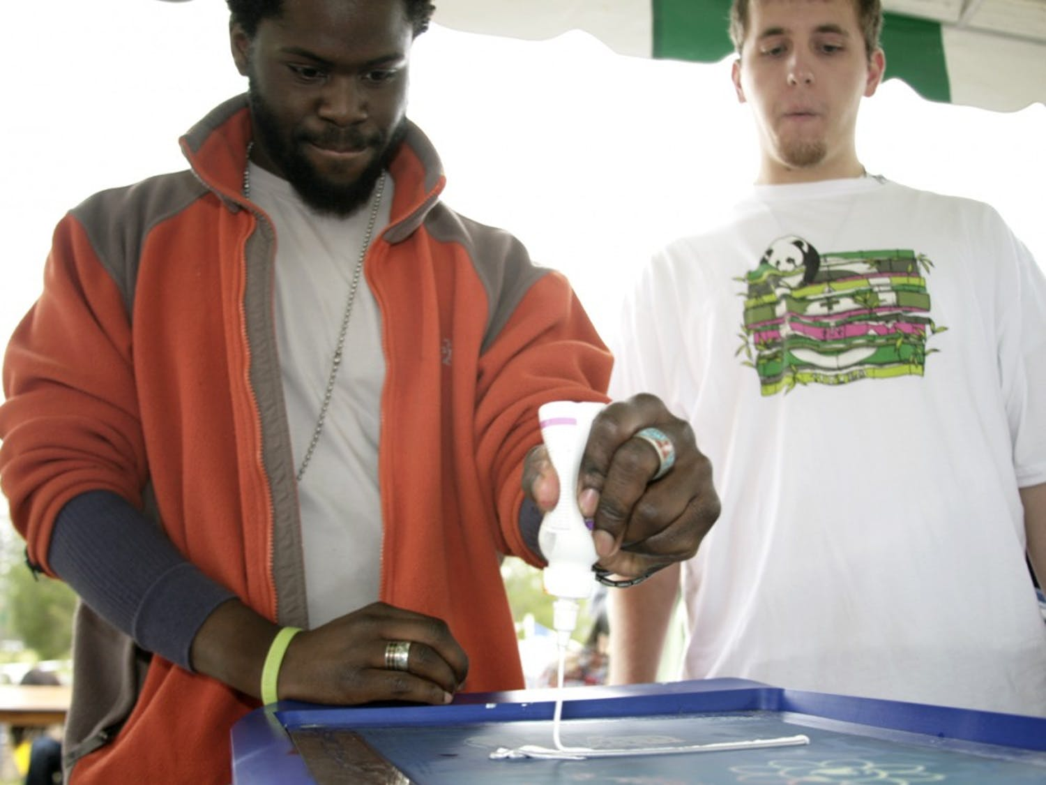 CJ Suitt, of Chapel Hill, screen presses a shirt found at the Swap-O-Rama-Rama, an event that encouraged the trade and creative re-use of clothing at Earth Action Day on Saturday at the Southern Community Park. Suitt and Jake Jacoby (right) are cofounders of Sacrificial Poets, a group that performs spoken-word poetry and works with high school students in Chapel Hill, and performed at the event.