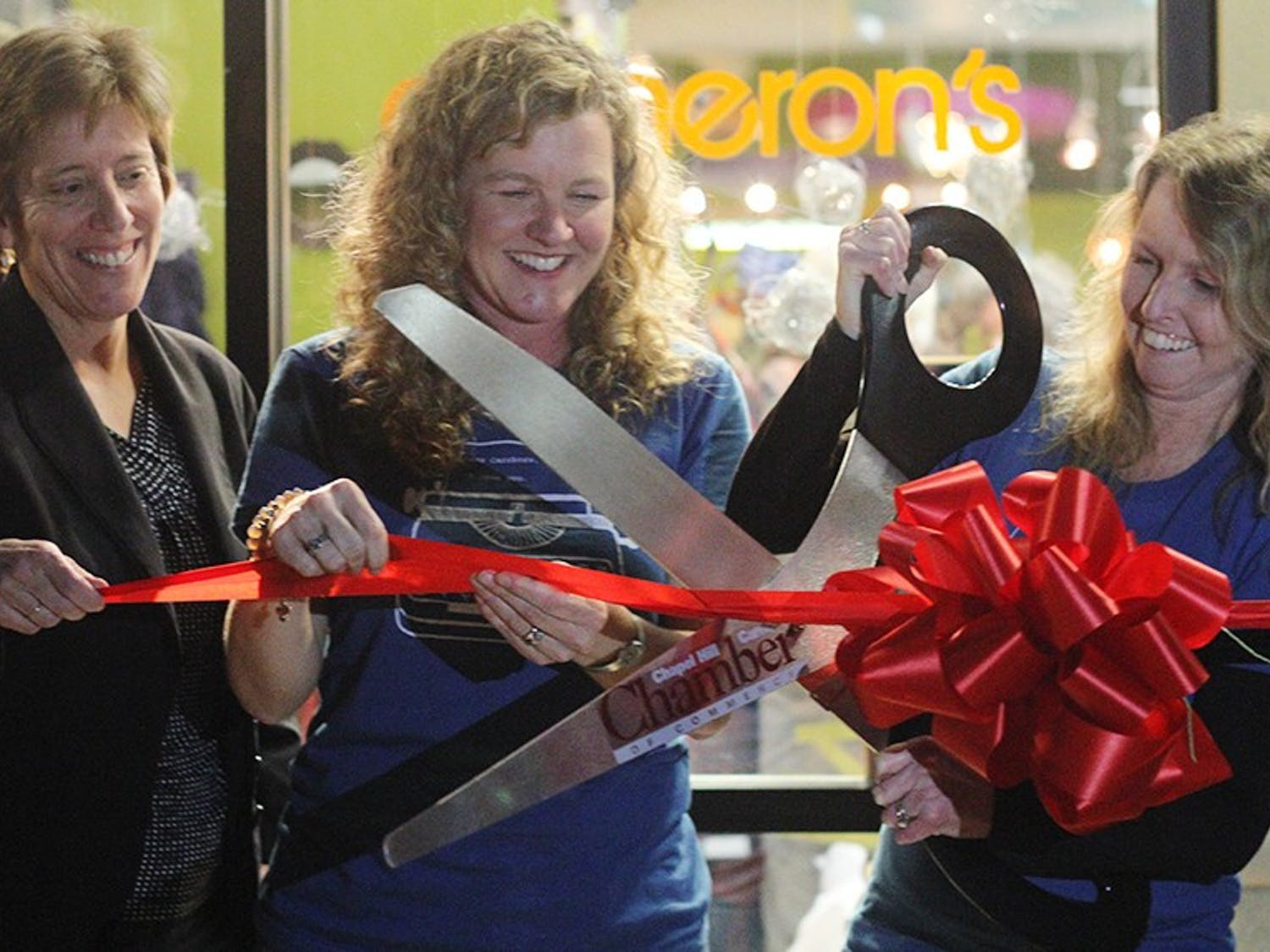 Carrboro Mayor Elect Lydia Lavelle cuts the ribbon at the grand opening of Cameron's with co-owners Wendy Smith and Bridget Pemberton-Smith. Cameron's is the first business to move into 300 East Main.