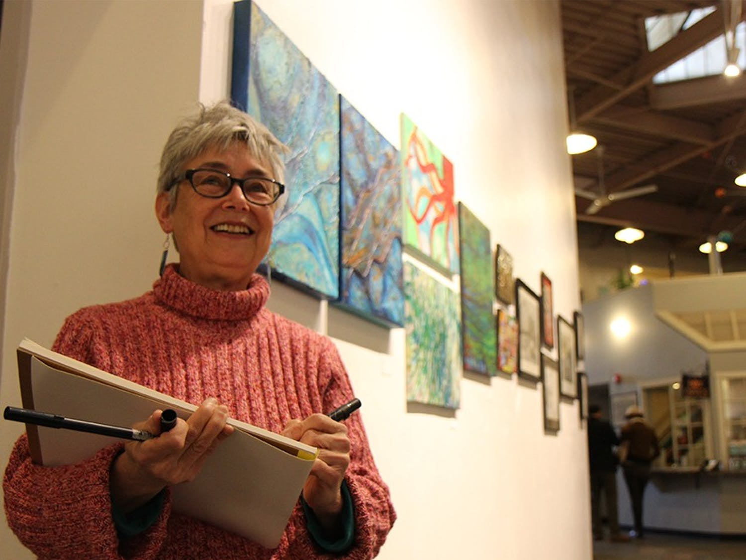Maja K., a resident of Chatham County, creates a sketch of the visitors at the ArtsCenter's Annual Student Exhibit, where some of her own work is being displayed. She is a member of the Triangle Sketch Crawl, a group of local sketchers of all skill levels who explore the Triangle area through their art.
