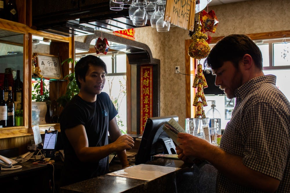 <p>Kevin Wang, age 36 and owner of the Jade Palace restaurant, takes a customer's order on Tuesday, Oct. 1, 2019.&nbsp;</p>