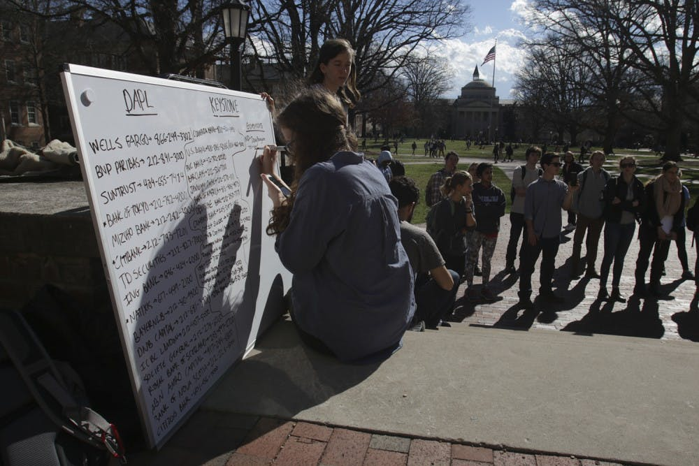 <p>Sophomore Emma Hennen writes down the&nbsp;phone numbers of senators and organizations to call to discuss stopping the construction of the Dakota Access and Keystone XL pipelines.</p>