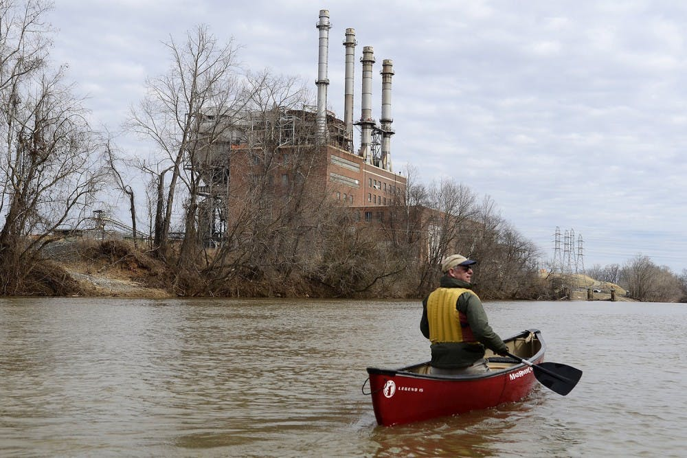 Mark Bishopric, a managing partner of Three Rivers Outfitters, paddles past the Duke energy Dan River Steam Station Tuesday. Coal ash was leaked into the river below the steam station. The Dan River in Eden, N.C. was running high Tuesday, February 25, 2014. New estimates by a team of experts using a drone say a coal ash pond at Duke Energy's Dan River Steam Station leaked at least 35 million gallons tons of coal ash into the Dan River after a drainage pipe running beneath the coal ash pond failed pouring the substance into the waterway. (John D. Simmons/Charlotte Observer/MCT)