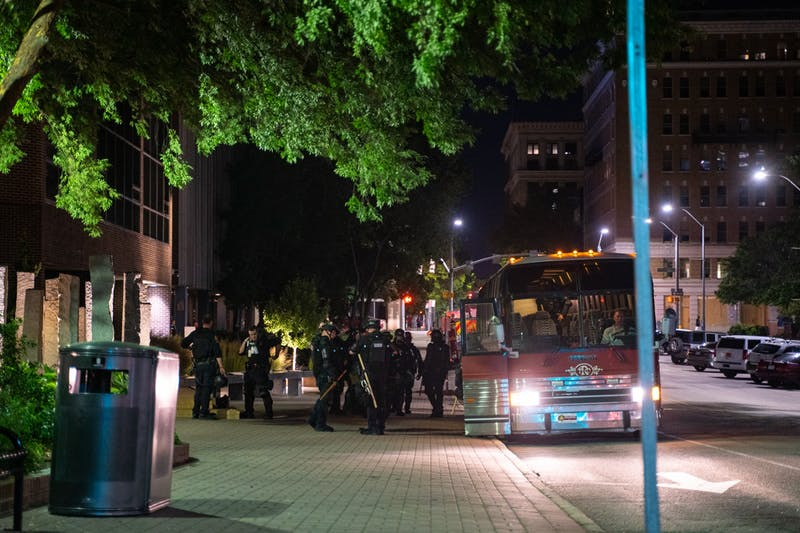 More than ten Raleigh police officers dressed in riot gear exit a bus in downtown Raleigh minutes before the 10 p.m. city curfew during the Black Lives Matter protest on Friday, Aug. 28, 2020.