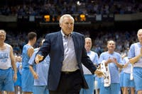 Surrounded by decades of former University of North Carolina players, UNC coach Dean Smith acknowledges a standing ovation from the crowd after being honored during the Celebration of a Century at the Smith Center in Chapel Hill, North Carolina, Friday, February 12, 2010. This is the 100th year of Carolina basketball. (Robert Willett/Raleigh News & Observer/MCT)