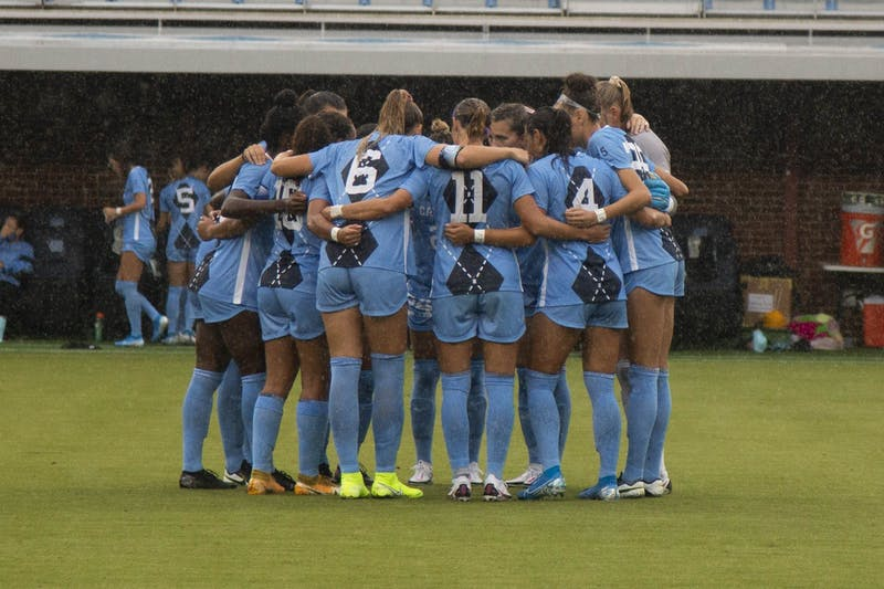 UNC women's soccer team huddles before the start of their game against Wake Forest at Dorrence Field on Thursday, Sep. 17, 2020. UNC defeated Wake Forest with a final score of 4-1. Two of the goals were scored by junior forward Brianna Pinto, number eight, and the other two by junior forward Rachel Jones, number 10.