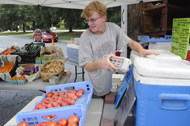 """Ben Bergmann, a farmer from Fickle Creek Farm, has been a participant of the Chapel Hill Market for 12 years.   Taking place in the parking lot of University Mall, the market is has moved its location several times.  With the prospect of having a permanent home, Bergman says, """"I wish it could be here permanently but it's a little tenuous to be honest.  It would be nice if we had a longer term commitment from the mall."""""""