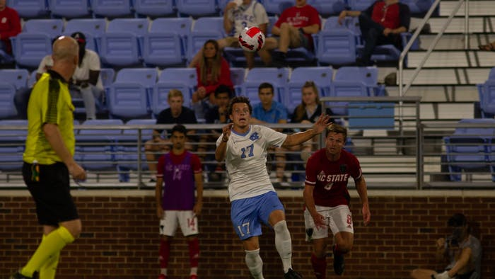 UNC junior midfielder Cameron Fisher (17) headbutts the soccer ball in the game against NC State at Dorrance Field on Oct. 3. The Tar Heels won 4-0.