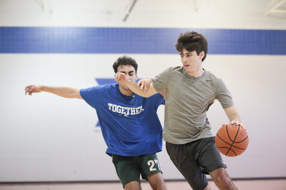 <p>Ryan Wilcox (right), sports editor of The Daily Tar Heel, dribbles past a Duke Chronicle staffer during a scrimmage in Brodie Recreation Center on Duke's campus on Sunday, Jan. 26, 2020. The Daily Tar Heel beat the Chronicle three games to one.</p>