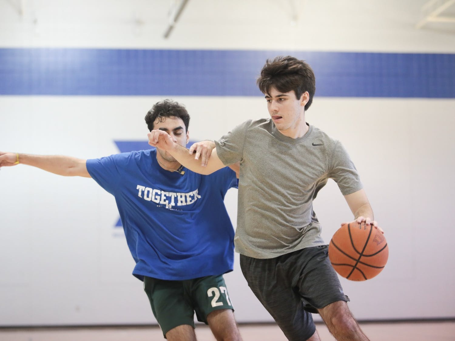 Ryan Wilcox (right), sports editor of The Daily Tar Heel, dribbles past a Duke Chronicle staffer during a scrimmage in Brodie Recreation Center on Duke's campus on Sunday, Jan. 26, 2020. The Daily Tar Heel beat the Chronicle three games to one.