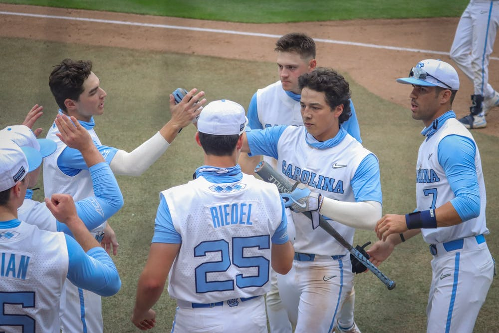 UNC sophomore outfielder Angel Zarate (40) is congratulated by his teammates for his home run during the Tar Heels' 1-6 loss against N.C. State on Saturday, March 27, 2021 in Boshamer Stadium in Chapel Hill, N.C. Zarate's home run was UNC's only score during the game.