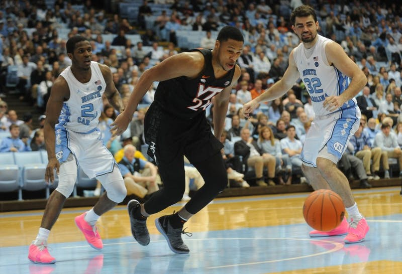 Virginia Tech redshirt junior forward Kerry Blackshear, Jr., dives for the ball as  UNC senior guard Kenny Williams (24) and UNC senior forward Luke Maye (32) give chase at the Smith Center on Monday, Jan. 21, 2019. The Tar Heels won 103-82.