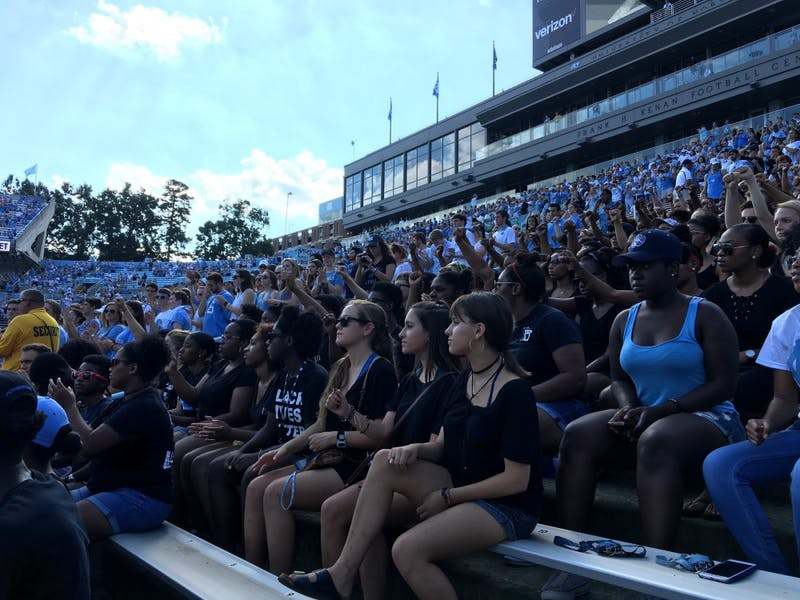 "While ""The Star-Spangled Banner"" played in Kenan Stadium Saturday, protestors remained seated and raised their fists."