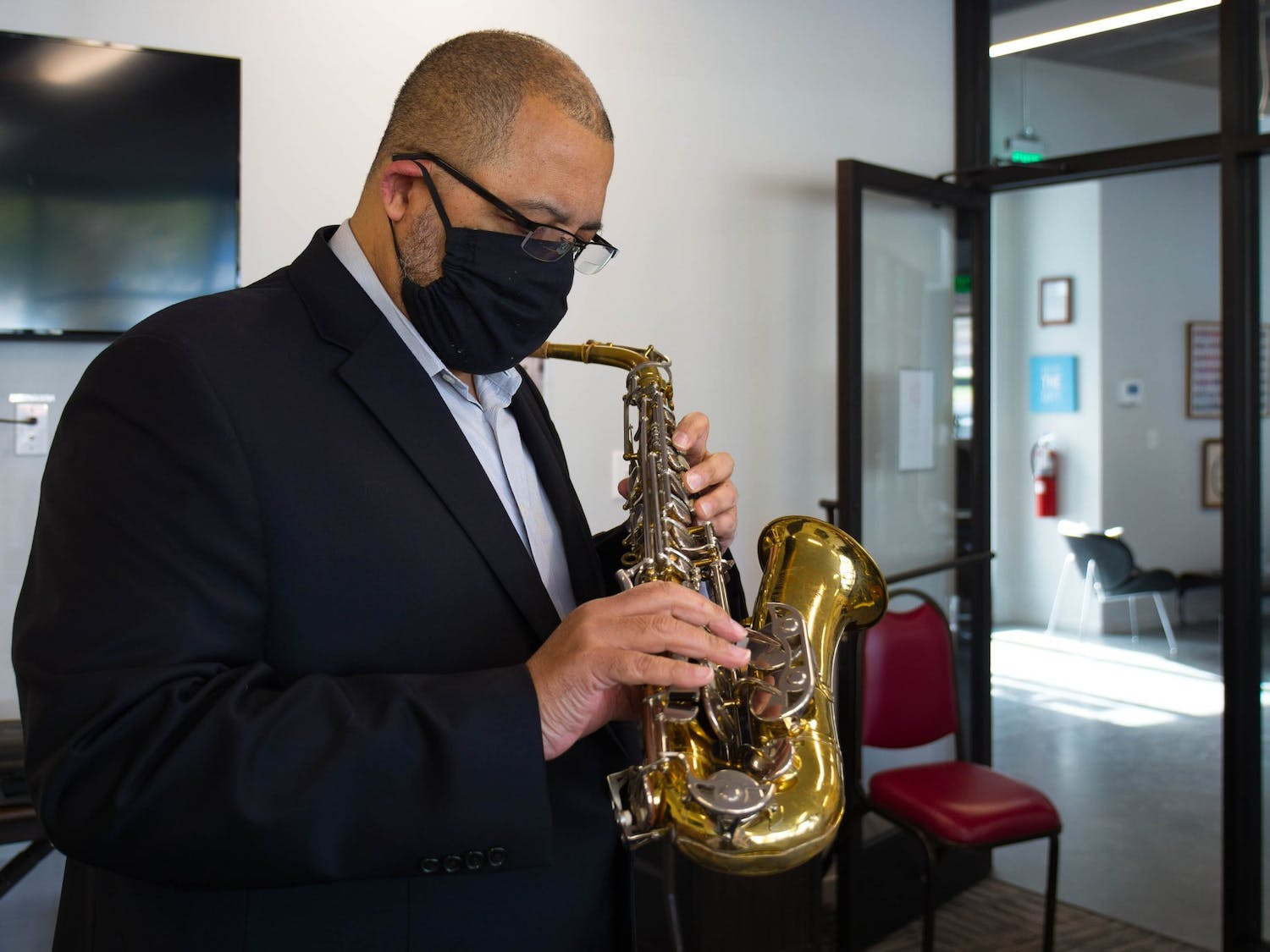 Ralph Barrett, an Assistant Professor of NC Central University's Music Department, tests the condition of the pads on a donated saxophone in the YouthWorx conference room on Wednesday, Dec. 9, 2020. Barrett is a member of Musical Empowerment's Board of Directors.