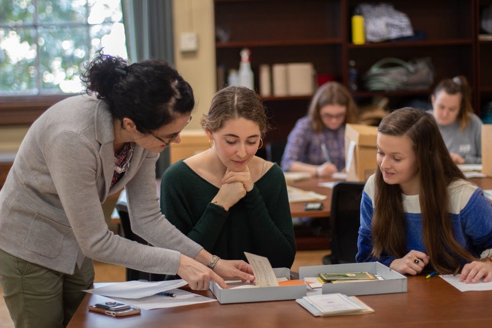 <p>Emily Orland, a DTH staffer and first-year history and media and journalism double major, and Brynn Garner, a junior environmental science and history double major, are instructed by Professor Katherine Turk in Wilson Library on Thursday, Jan. 16, 2020.&nbsp;</p>
