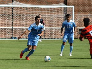 Senior midfielder and captain Mauricio Pineda (2) dribbles the ball while junior midfielder Raul Aguilera (28) watches during a game against Syracuse at Dorrance Field on Saturday, Oct. 12, 2019. The Tarheels lost 3-4.
