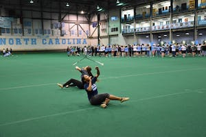 UNC majorettes Ava Smith (left) and Ciara Gillis (right) rehearse during marching band practice in the Eddie Smith field house.