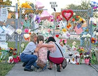 Shari Unger kisses Melissa Goldsmith as Giulianna Cerbono lights candles at a memorial at Marjory Stoneman Douglas High School on Sunday, February 18, 2018. A large number of people visited the site to honor the students and teachers killed in a shooting spree on Wednesday, February 14, 2018. (Charles Trainor Jr./Miami Herald/TNS)