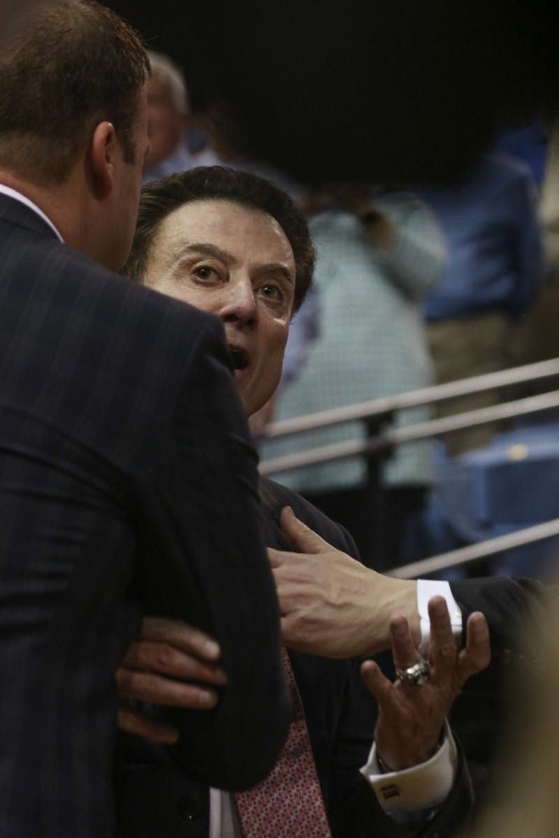 "Louisville head coach Rick Pitino is held back by his assisant coaches after reacting to a North Carolina fan shouting ""you suck, Rick"" as the coach was walking into the locker room at halftime."