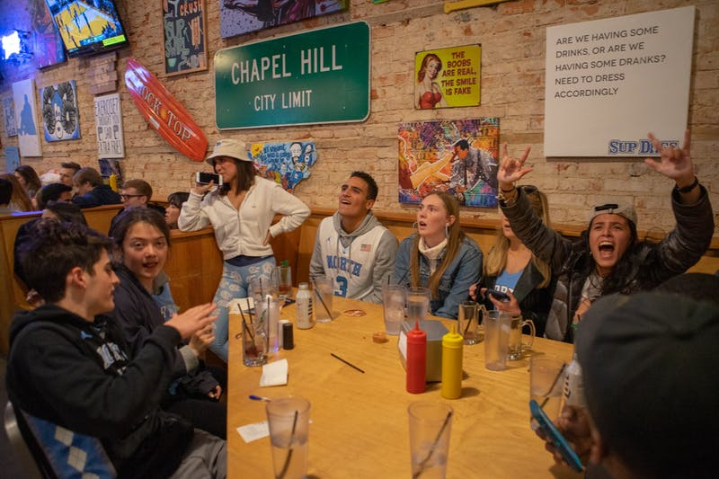 Spectators in Sup Dogs on Franklin Street cheer during UNC's game against Duke following the Tar Heels taking a 10-point lead on Sat. 8, 2020.  The Tar Heels lost to Duke 98-96 in overtime.