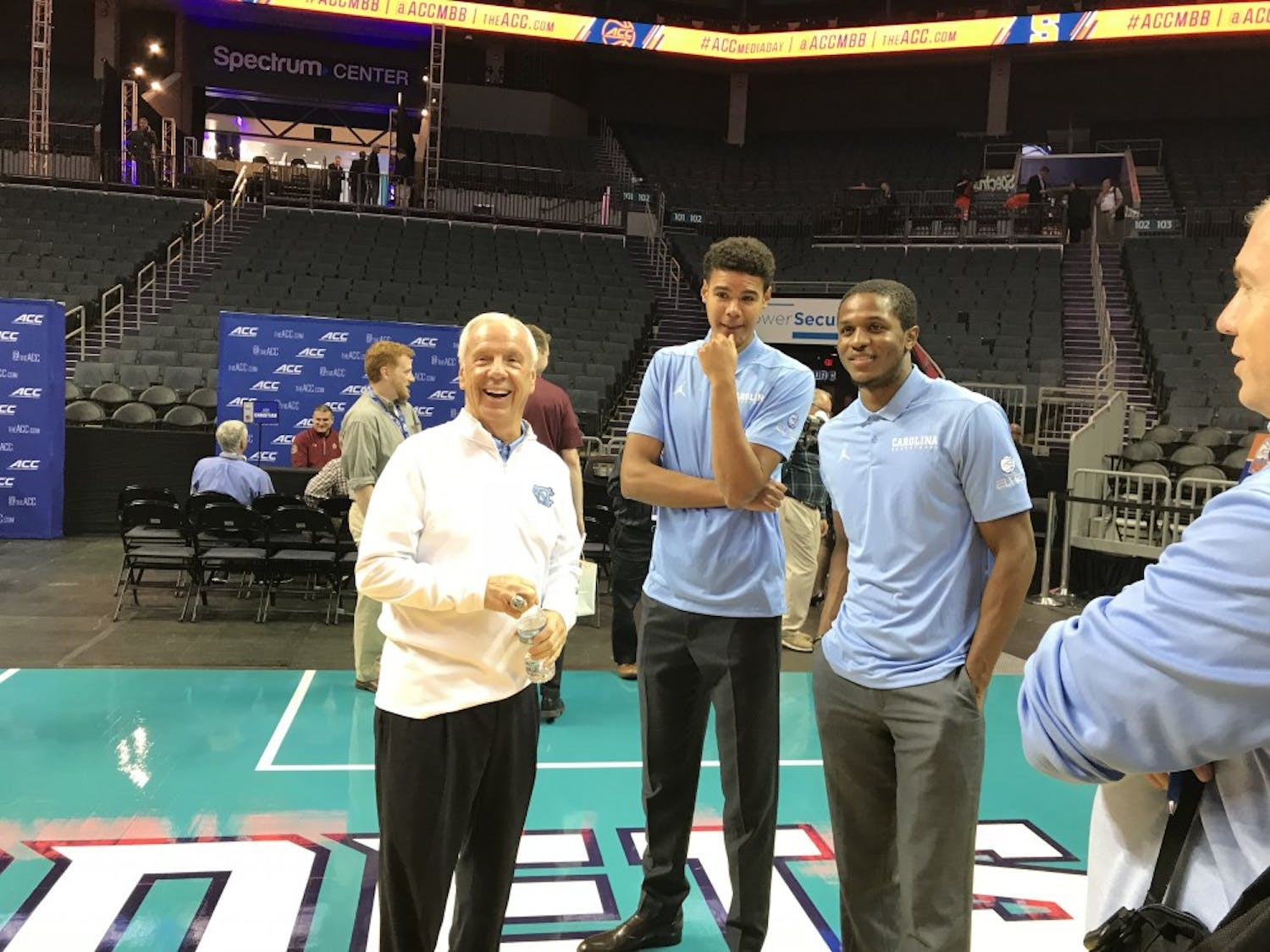 UNC head coach Roy Williams and guards Cameron Johnson and Kenny Williams pose at the Spectrum Center for ACC men's basketball media day on Oct. 24.