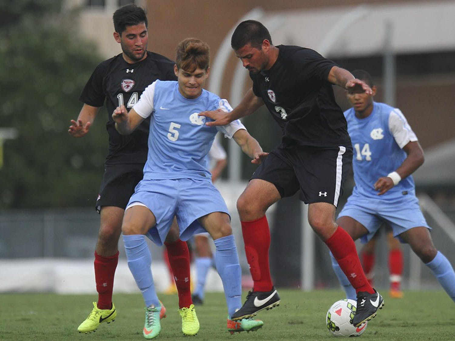 UNC forward, Alan Winn (5), makes a play on the ball against Gardner-Webb defender Matt Bogart (3) and mid-fielder Patrick Gurser (14).  Winn would finish the match with a goal early in the second half.  UNC defeated Gardner-Webb 7-0 Friday night at Fetzer field in an exhibition game.