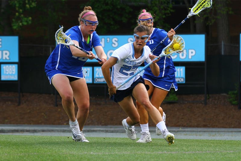 Aly Messinger (27) drives past Duke's Isabelle Montagne (18) and Claire Scarrone (19).