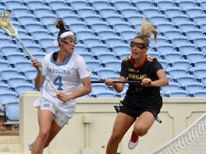 Midfielder Marie McCool (4) charges past Maryland defender Jen Giles (5) on Feb. 24 in Kenan Stadium.