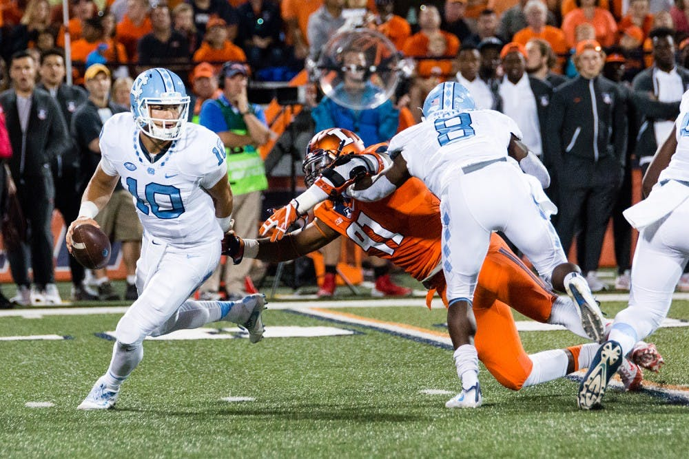 North Carolina quarterback Mitch Trubisky (10) dodges a tackle from Illinois defensive lineman Dawuane Smoot (91) during the game against Illinois at Memorial Stadium on Saturday, September 10. The Tar Heels won 48-23.