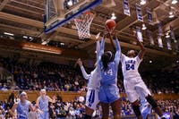 Duke forward Onome Akinbode-James (24) attempts to shoot for the basket against UNC sophomore center Janelle Bailey (44) in Cameron Stadium on Sunday, March 3, 2019.The Tar Heels lost to the Blue Devils with a score of 44-62.