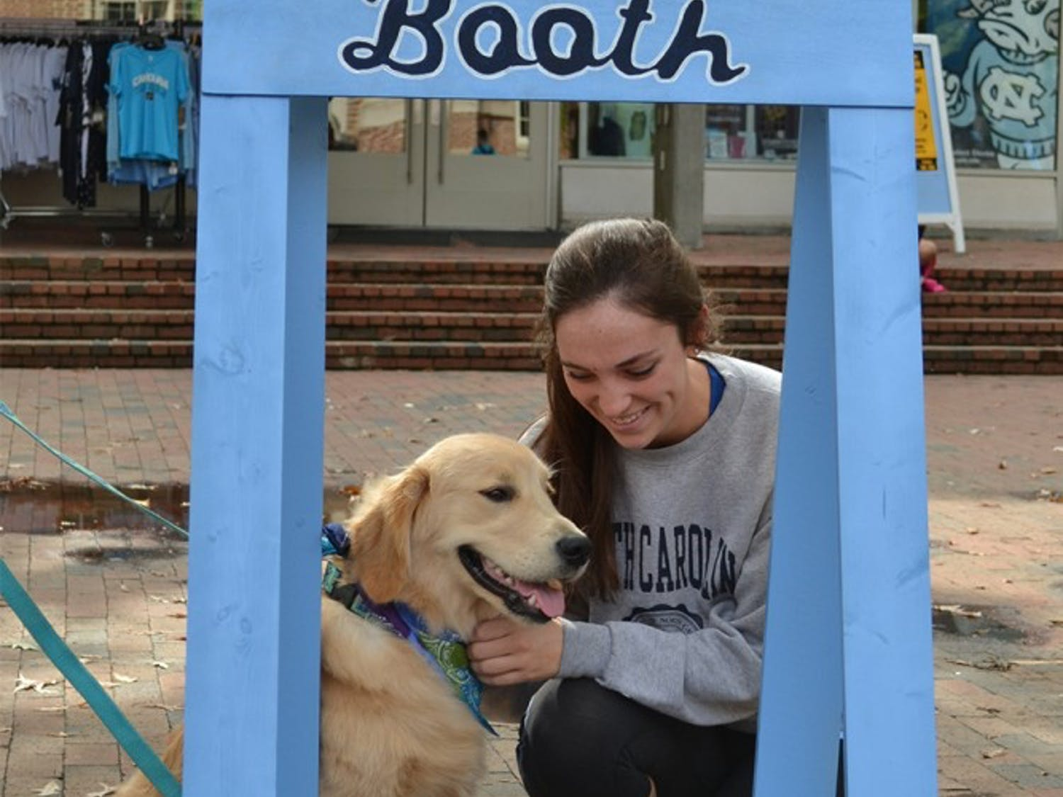 UNC junior Kirsten Wiedbusch shares a moment with Holden the Golden Retriever at the Helping Paws Puppy Kissing Booth.