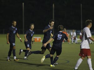 Alex Rose (21) celebrates a goal with teammate John Nelson (5). The North Carolina men's soccer team defeated Rutgers, 6-1, on Sunday night in Cary.
