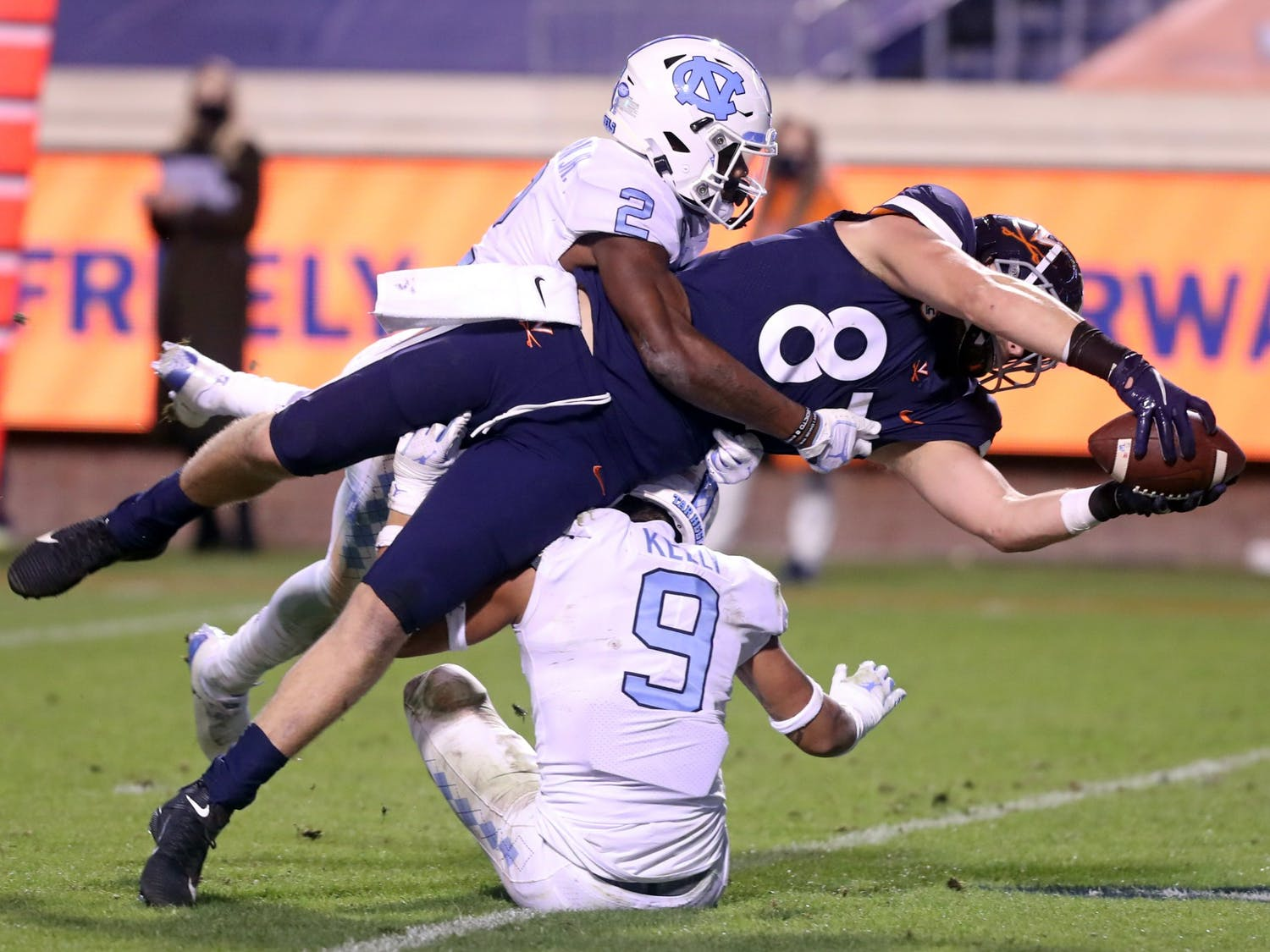 Virginia tight end Tony Poljan (87) reaches between North Carolina Tar Heels defensive back Don Chapman (2) and North Carolina defensive back Cam'Ron Kelly (9) for a touchdown during the game Saturday in Charlottesville, Va. Virginia defeated North Carolina 44-41. Photo courtesy of Andrew Shurtleff for the Daily Progress via the ACC