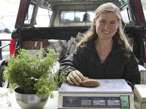 Jamie Murray, owner of Sunset Farms in Snow Camp, weighs potatoes at the Carrboro Farmers' Market, which is funded by donations.