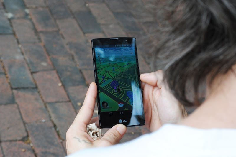 Chapel Hill resident Brandon Lee plays Pokemon GO in front of the Old Well Tuesday morning.