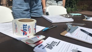 Several student volunteers work a table in the Pit to assist others in registering to vote on Oct. 1, 2019.