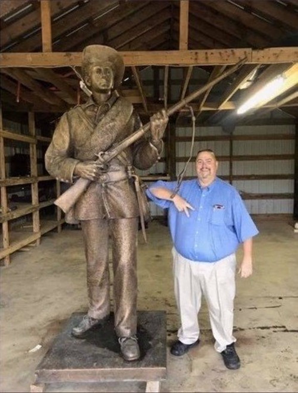 "<p>Kevin Stone, commander of the Sons of Confederate Veterans' North Carolina chapter, poses next to Silent Sam after suing and immediately settling with the UNC System and Board of Governors, a deal that gave the group possession of the Confederate monument and $2.5 million in UNC System money for its ""preservation and benefit."" Photo courtesy of SCV members.&nbsp;</p>"